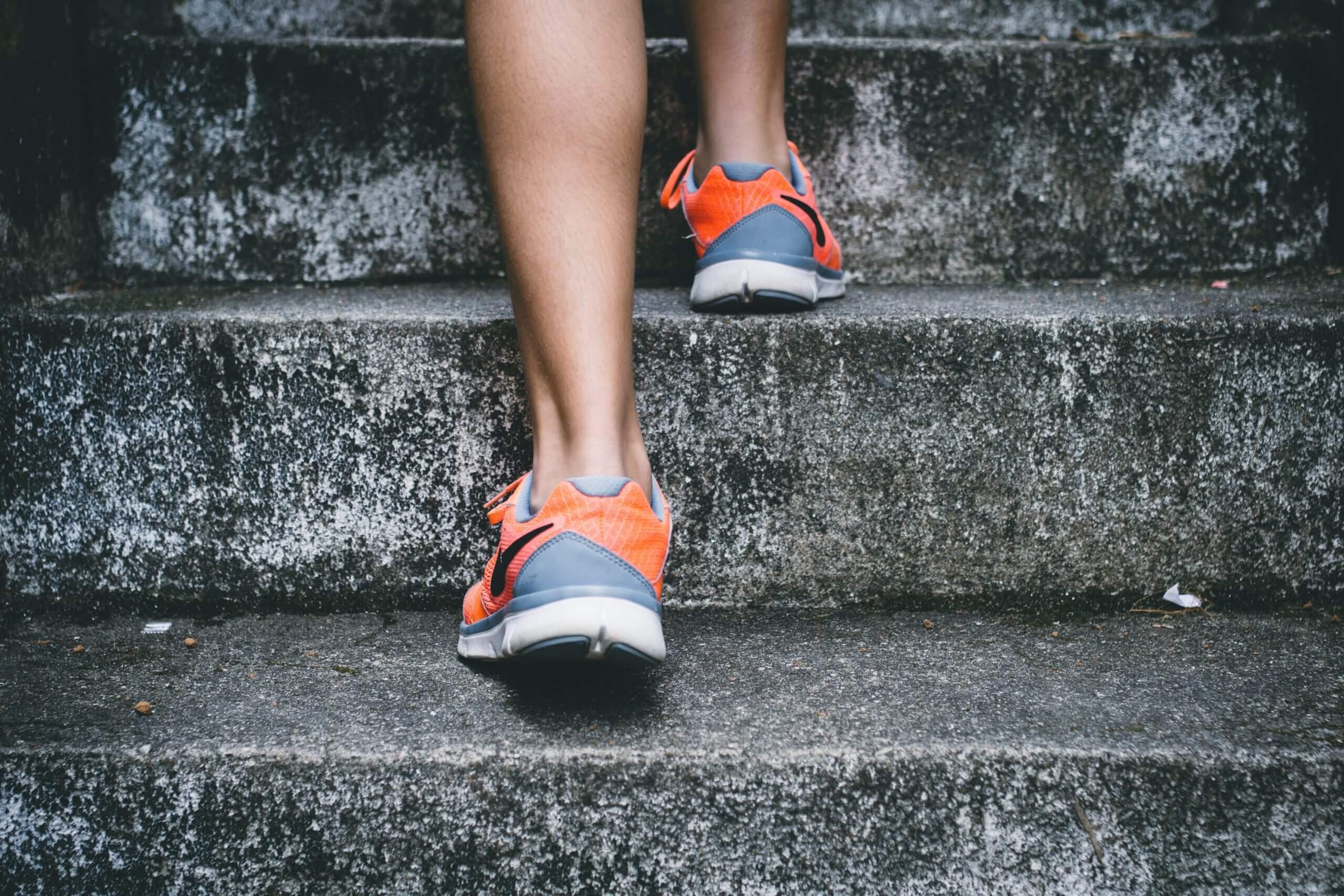 Vue sur les baskets d'une femme en train de monter les escaliers