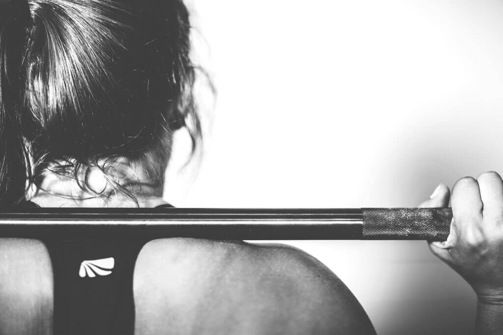 femme prise de dos avec une barre de musculation sur les épaules